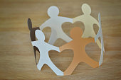 Paper people in a circle holding hands - Anti-racism and love concept