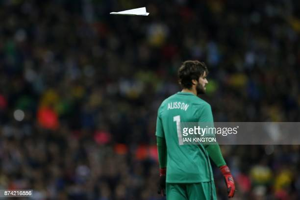 A paper plane flies behind Brazil's goalkeeper Alisson during the second half of the international friendly football match between England and Brazil...