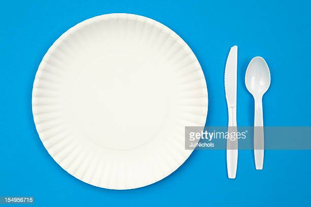 A paper plate next to plastic utensils on a blue table