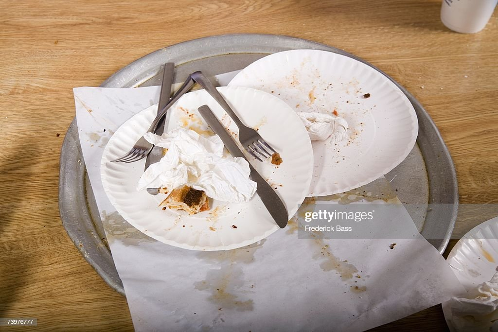 Paper plates and cutlery piled on a canteen tray