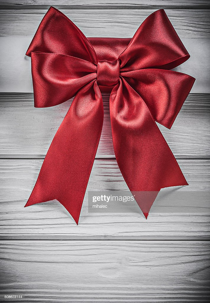 Paper roll with red bow on wooden board holidays concept : Stock Photo