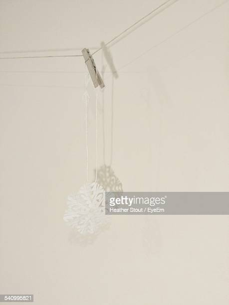 Paper Snowflake Hanging Against White Wall