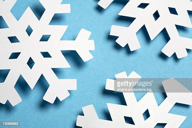 Paper snowflakes on blue background (close-up)