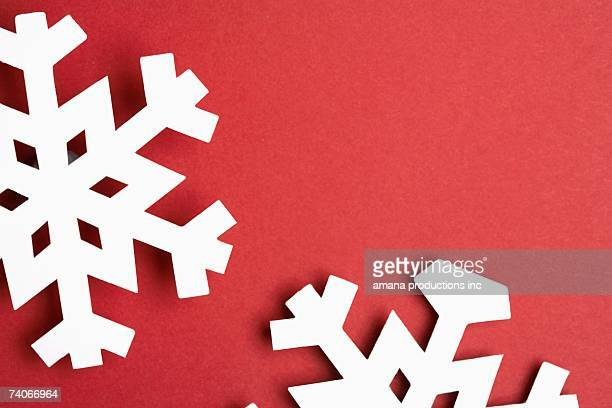 Paper snowflakes on red background (close-up)