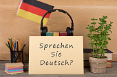 Learning languages concept - paper with text 'sprechen sie deutsch?', flag of the Germany, books, headphones, pencils on wooden background