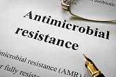 Paper with words antimicrobial resistance AMR and glasses. Medical concept.
