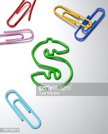Paperclips on a desk one bent into a Dollar symbol : Stock Photo