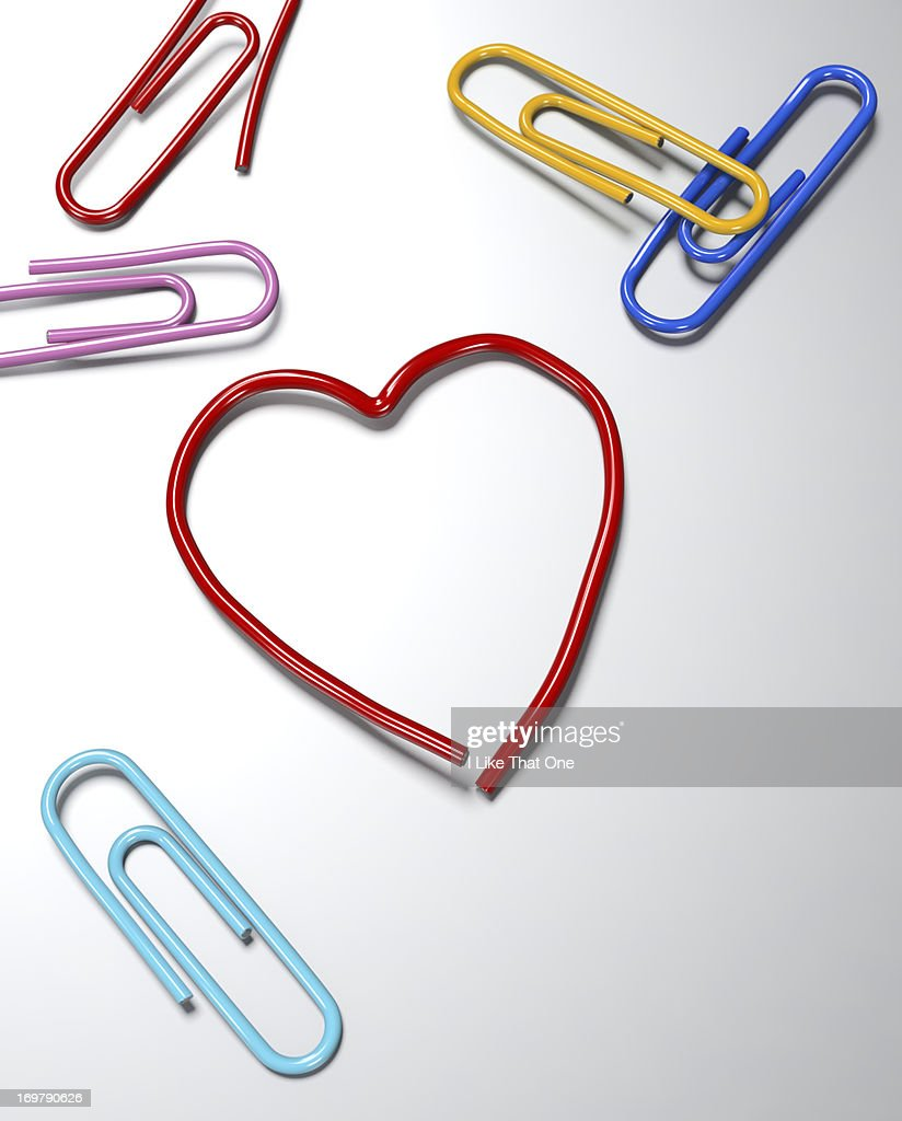 Paperclips on a desk one bent into a Heart symbol : Stock Photo