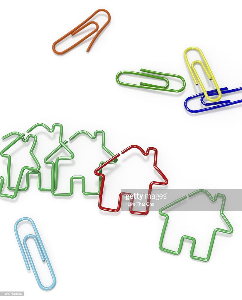 Paperclips on a desk some bent into House symbols : Stock Photo