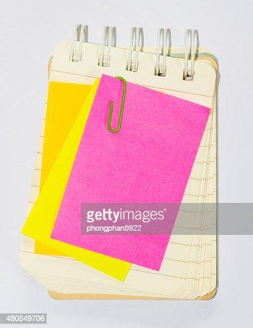 Pós-paperclips e nota livro sobre fundo branco, : Foto de stock