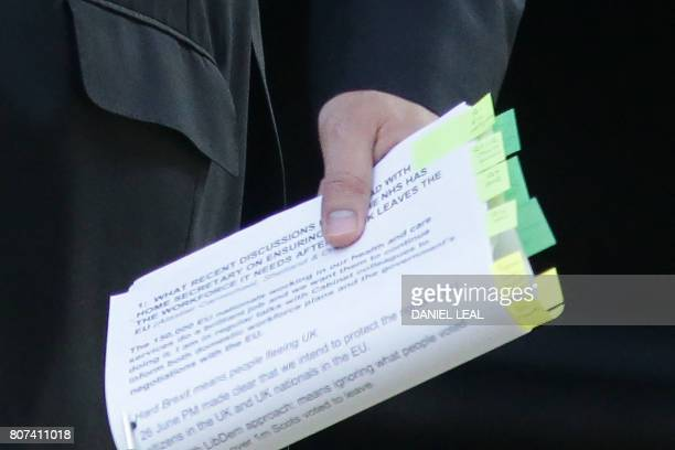 Papers are held by Britain's Health Secretary Jeremy Hunt as he arrives for a Cabinet meeting at 10 Downing Street in central London on July 4 2017 /...