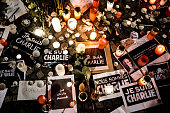 Papers with 'I am Charlie' in various languages displayed are left near candles at a vigil in front of the French Embassy following the terrorist...