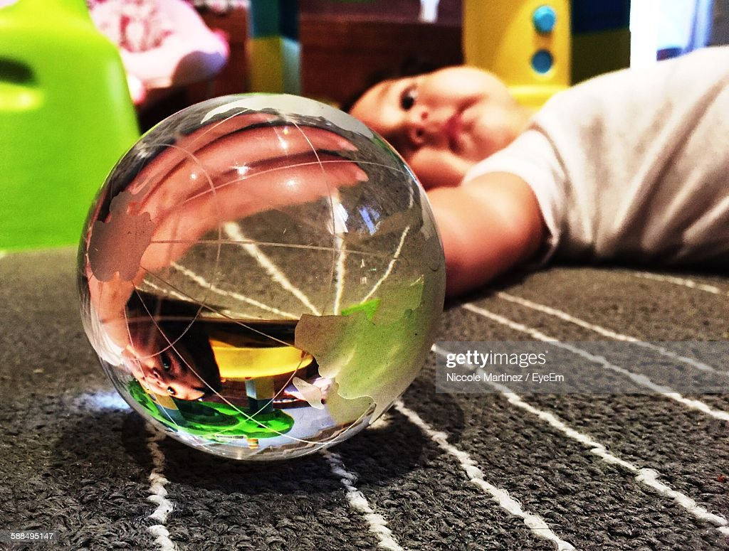 Paperweight By Baby Girl Lying On Carpet At Home