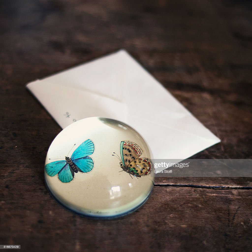 Paperweight on letter envelope on wooden table