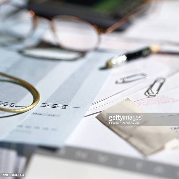 Paperwork, glasses and office materials lying on desk.