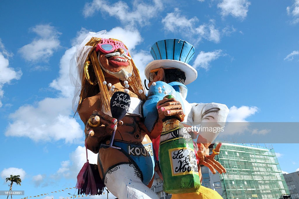 Papier-mache figures, dressed up in wedding costumes, representing King Vaval and mocking France's right-wing opposition UMP leader Jean-Francois Cope and former prime minister Francois Fillon are pictured during the Carnival parade in the streets of Fort-de-France on the French Caribbean island of Martinique, on February 10, 2013. The Carnaval started on February 9, 2013 and will run until Ash Wednesday on February 13, 2013 when Vaval, a giant papier-mache figure symbolizing the king of the carnival, is burned.