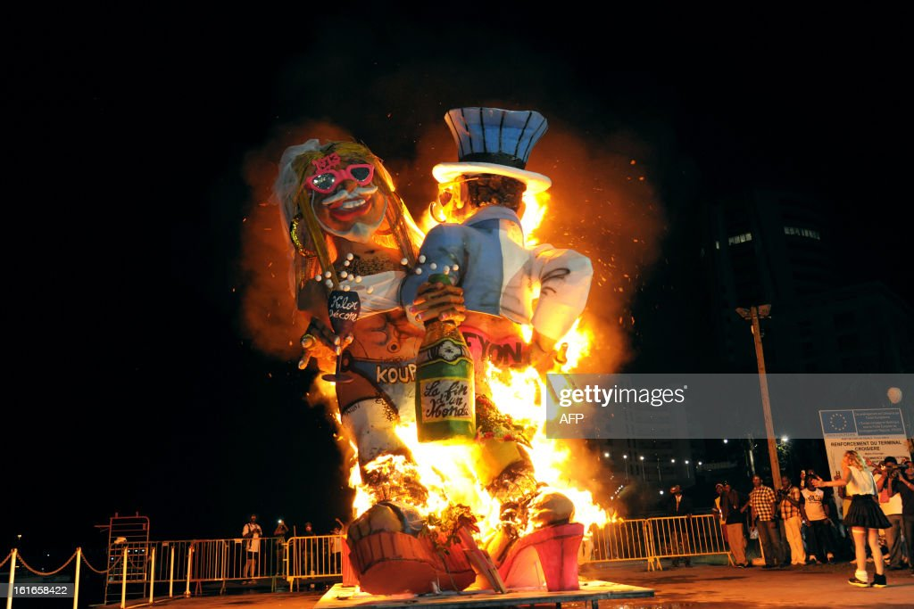 Papier-mache figures, dressed-up in wedding costumes, representing King Vaval and mocking France's right-wing opposition UMP leader Jean-Francois Cope (L) and former Prime minister Francois Fillon are burning at the end of the Carnival parade in Fort-de-France on the French Caribbean island of Martinique, on February 14, 2013..
