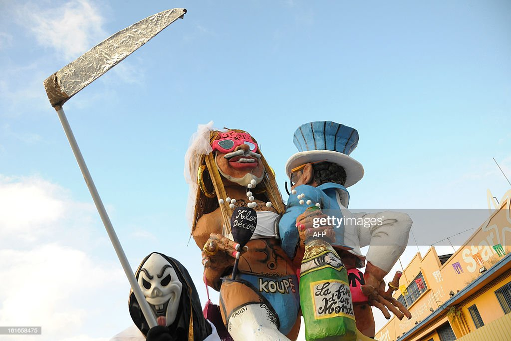 Papier-mache figures, dressed-up in wedding costumes, representing King Vaval and mocking France's right-wing opposition UMP leader Jean-Francois Cope (L) and former Prime minister Francois Fillon parade before being burnet at the end of the Carnival parade in Fort-de-France on the French Caribbean island of Martinique, on February 14, 2013. (Figure at C holds a fake lollypop reading 'Klor Decone', referring to the Chlordecone pesticide heavily used in banana plantations in Martinique and Guadeloupe).