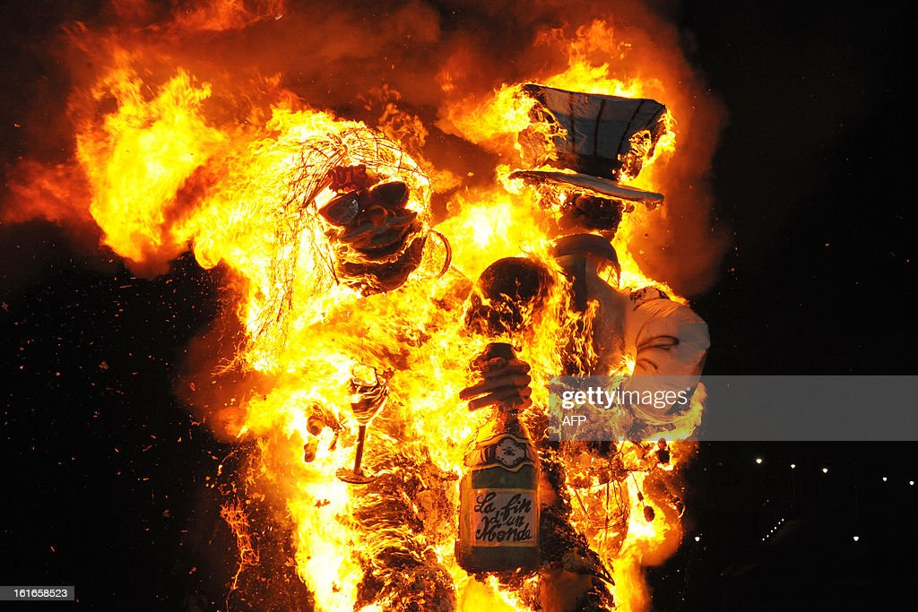 Papier-mache figures, dressed-up in wedding costumes, representing King Vaval and mocking France's right-wing opposition UMP leader Jean-Francois Cope (L) and former Prime minister Francois Fillon are burning at the end of the Carnival parade in Fort-de-France on the French Caribbean island of Martinique, on February 14, 2013.