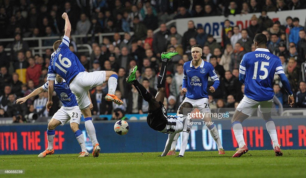 Papiss Cisse of Newcastle (C) attempts an overhead kick whilst being challenged by James McCarthy (L) of Everton, also seen is John Stones (28) and Sylvain Distin (15) also from Everton during the Barclays Premier League match between Newcastle United and Everton at St. James' Park on March 25, 2014, in Newcastle upon Tyne, England.