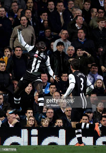 Papiss Cisse of Newcastle celebrates after scoring the opening goal with teammate Davide Santon during the Barclays Premier League match between...