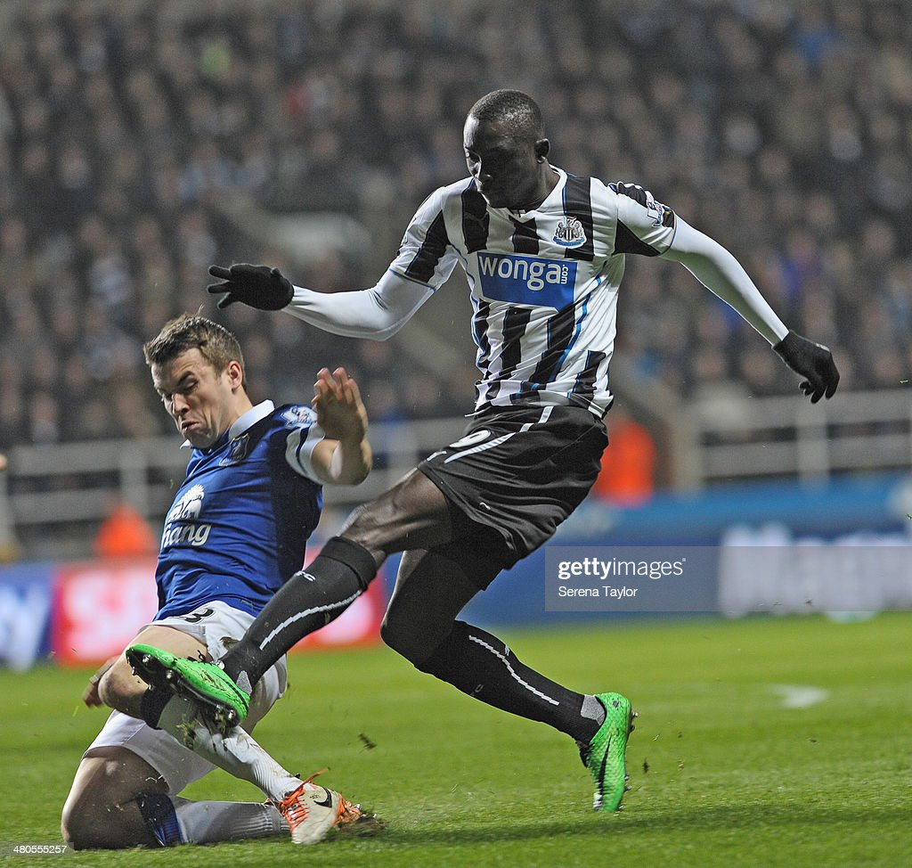 Papiss Cisse of Newcastle is challenged by Seamus Coleman of Everton during the Barclays Premier League match between Newcastle United and Everton at St. James' Park on March 25, 2014, in Newcastle upon Tyne, England.