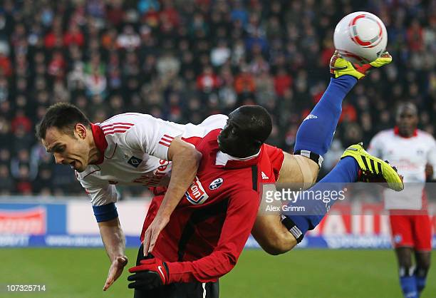 Papiss Demba Cisse of Freiburg is challenged by Heiko Westermann of Hamburg during the Bundesliga match between SC Freiburg and Hamburger SV at...