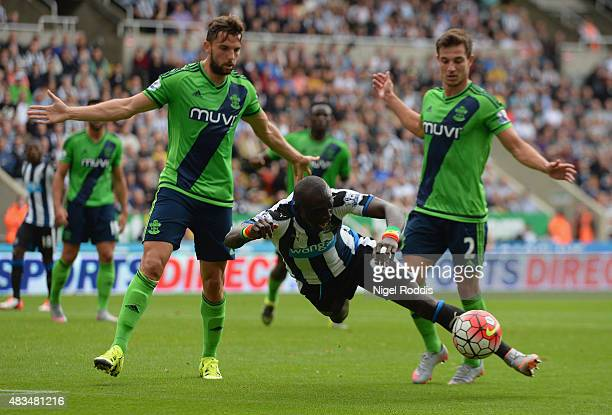 Papiss Demba Cisse of Newcastle United is challenged by Cedric Soares and Jay Rodriguez of Southampton during the Barclays Premier League match...