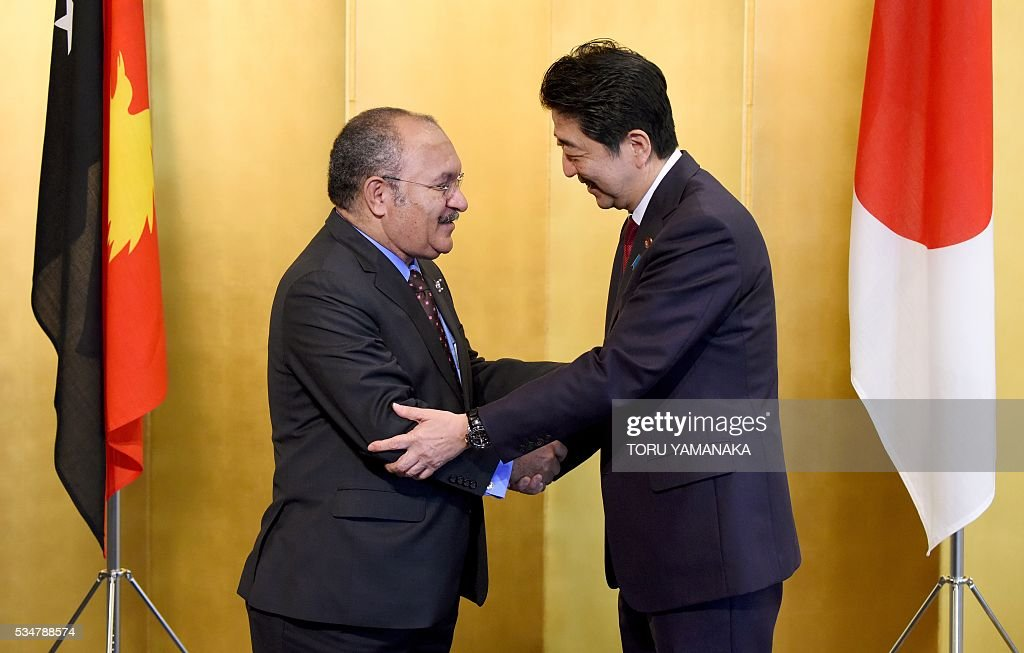 Papua New Guinean Prime Minister Peter O'Neill (L) is welcomed by Japanese Prime Minister Shinzo Abe (R) prior to their talks in Nagoya, central Japan, on May 28, 2016. O'Neill came to Japan to attend the Group of Seven (G7) summit meeting in Ise. / AFP / POOL / TORU