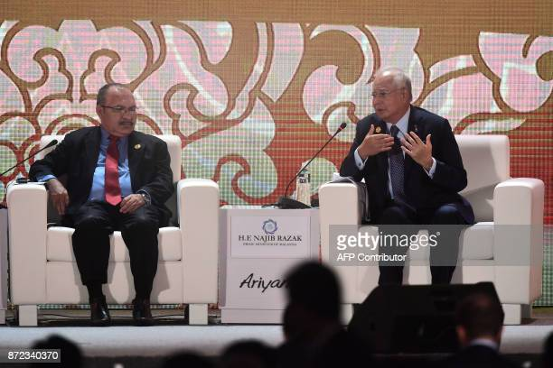 Papua New Guinea's Prime Minister Peter O'Neill listens as Malaysia's Prime Minister Najib Razak speaks during a dialogue on the final day of the...