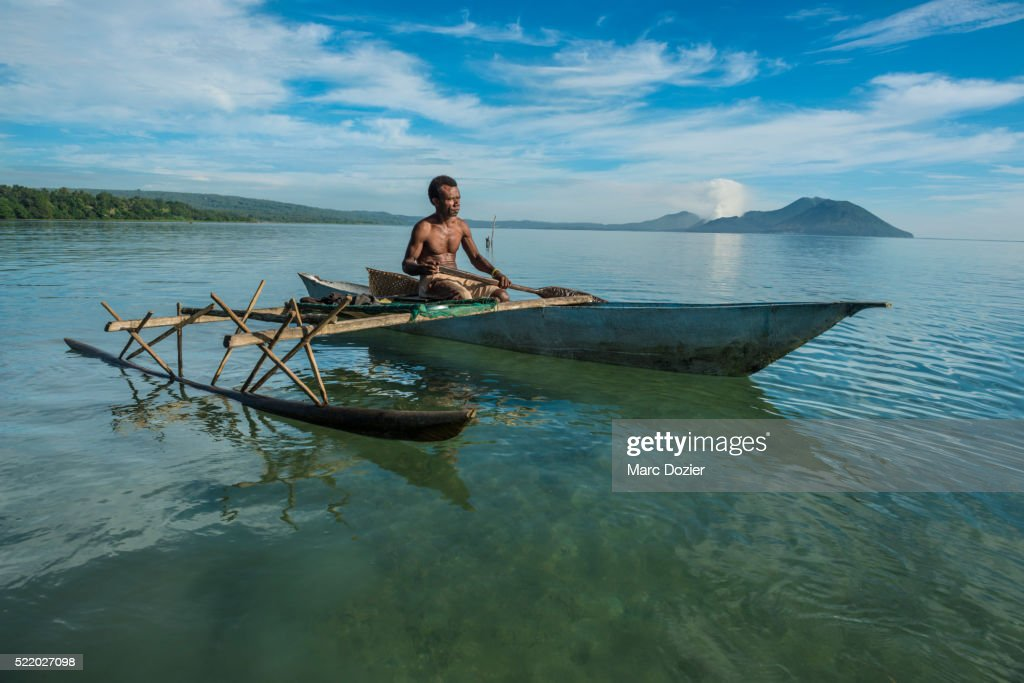 Papuan fisherman in front of volcanoes