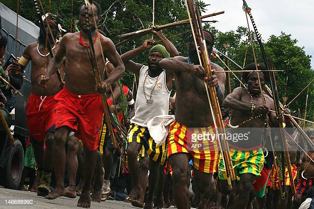 Papuan tribal warriors from Amole village some armed with poisoned bows and arrows launch an attack against tribesmen from the neigboring Harapan...
