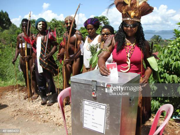 Papuan tribesmen and women wearing traditional costume vote in Jayapura on July 9 2014 located in remote eastern Indonesia's Papua province...