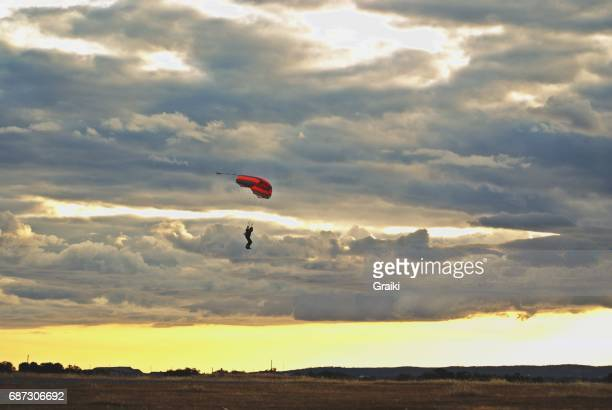 A parachute, sunset and a sky full of clouds.