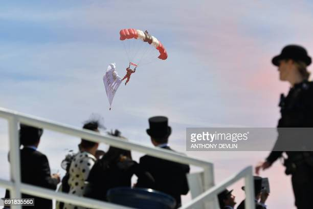 A parachutist flies past a tribune on the second day of the Epsom Derby Festival in Surrey southern England on June 3 2017 / AFP PHOTO / Anthony...