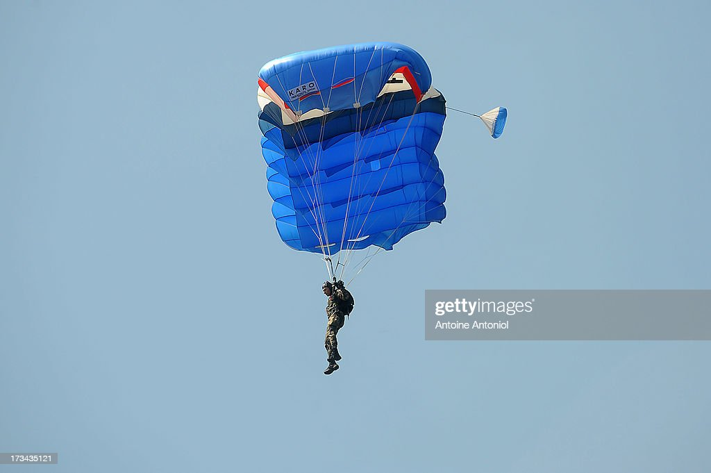 A parachutist lands during the Day parade on the Champs Elysees on July 14, 2013 in Paris, France. The annual military ceremony is the largest in Europe remembering the 'Fete de la Federation' for 1790.
