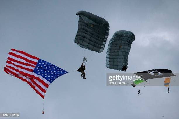 Parachutists display a US national flag as they jump over Carentan Normandy on June 5 a dayd ahead of the DDay ceremonie The commemorations will mark...