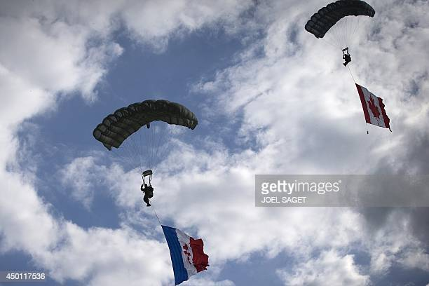 Parachutists display French and Canadian national flags as they jump over Carentan Normandy on June 5 a dayd ahead of the DDay ceremonie The...