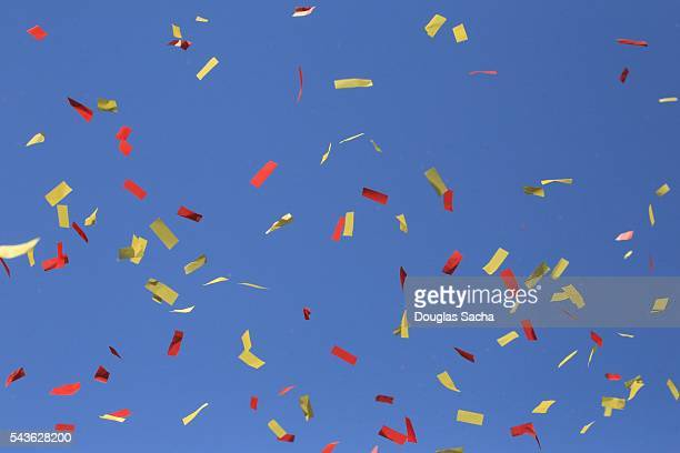 Parade Confetti falls against the clear blue sky