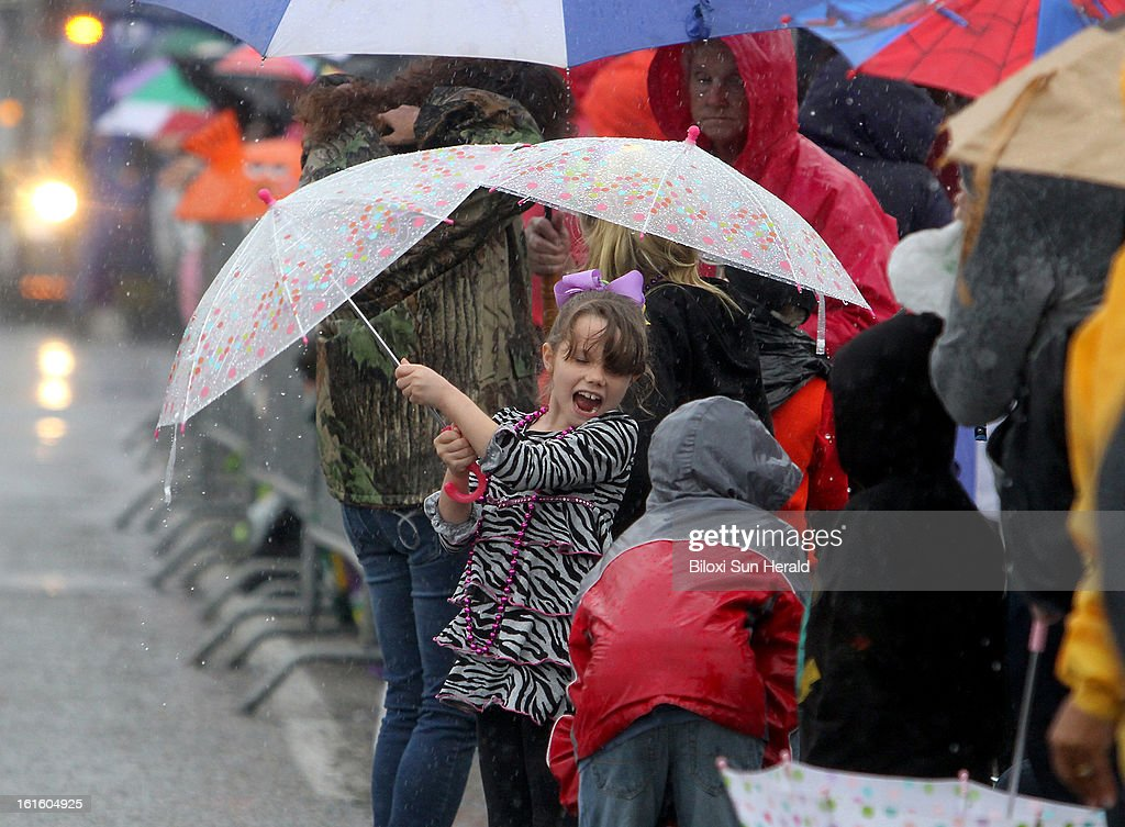Parade goers pull out umbrellas and brave the pouring rain as the Gulf Coast Carnival Association Parade rolls down Main Street in Biloxi, Mississippi, Tuesday, February 12, 2013.
