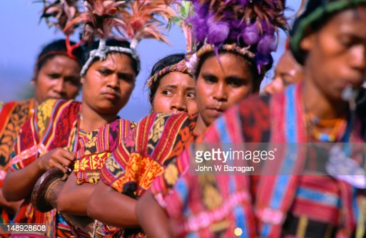 A parade of colourfully clad women performing a traditional Timorese dance.