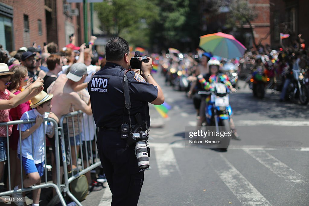Parade participants on motocycles being photographed by a police officer during the New York City Pride 2016 march on June 26, 2016 in New York City.