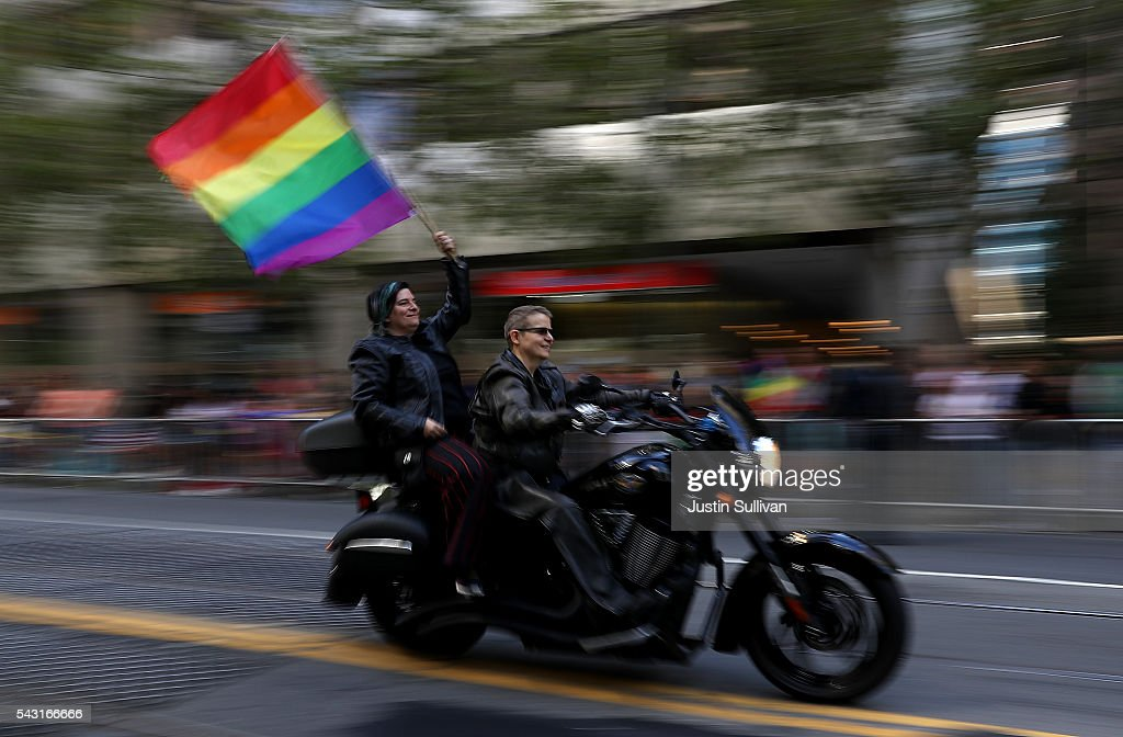 Parade participants wave a pride flag as they ride with the group Dykes on Bikes during the 2016 San Francisco Pride Parade on June 26, 2016 in San Francisco, California. Hundreds of thousands of people came out to watch the annual San Francisco Pride parade, one of the largest in the world.