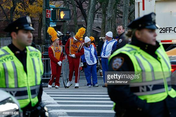 Parade participantss stand behind members of the New York City Police department before the annual Thanksgiving Day Parade on November 26 2015 in New...