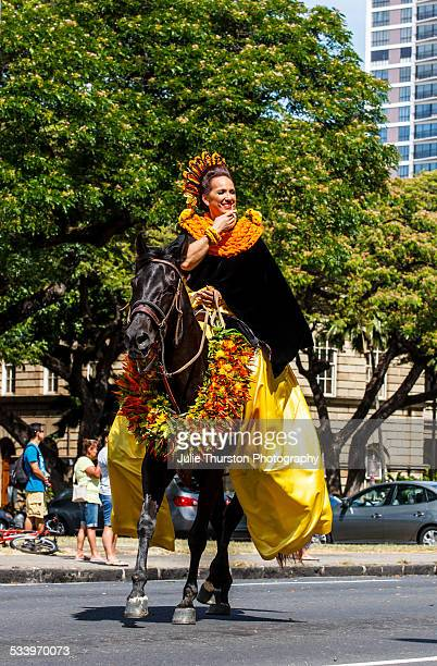 Parade Queen in Yellow Hawaiian dress and Flower Lei of one of the Hawaiian Islands riding on a horse adorned in a large Flower Garland during the...