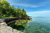 The clear waters of Lake Superior reveal large rocks and stones underwater. This cove, with pristine waters, is located near Au Train Michigan. Near Pictured Rocks National Lakeshore in the Upper Peni