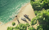 Top view of a couple sunbathing on a tropical island. Travel and vacation concept. This is a 3d render illustration