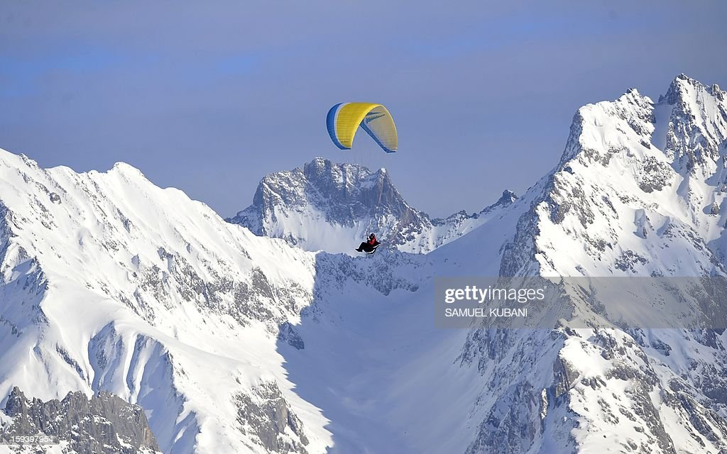 Paraglaider flies in mountains during the women's World Cup Super G on January 13, 2012 in St Anton am Arlberg. AFP PHOTO / SAMUEL KUBANI