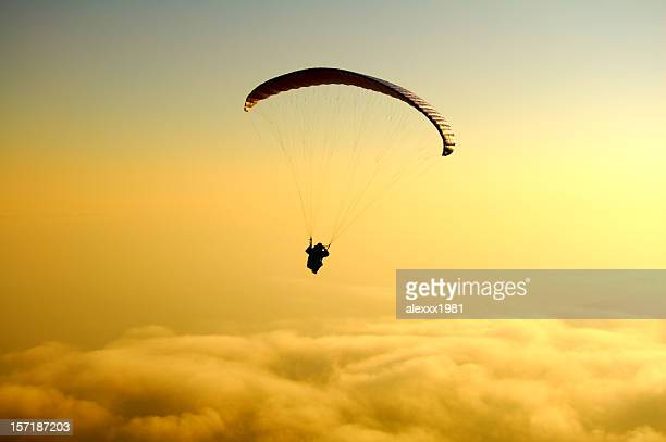 paraglide above yellow clouds on sunset