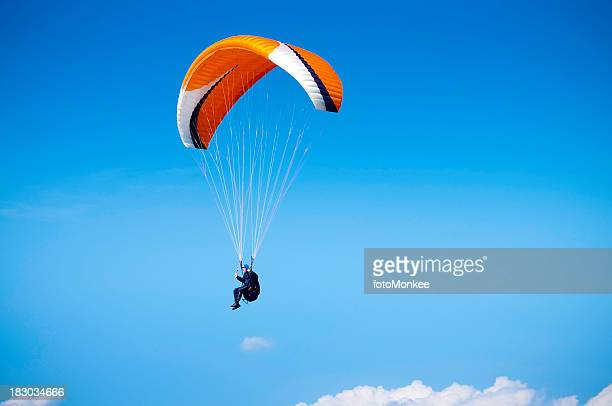 Paraglider, airborne against big blue sky, UK